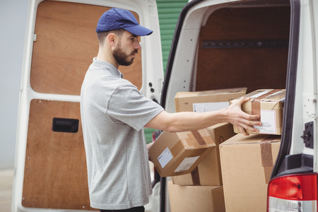 loading bay: Delivery man holding packages to load his van Stock Photo