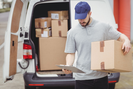 loading bay: Delivery man reading notes on his clipboard while holding package Stock Photo