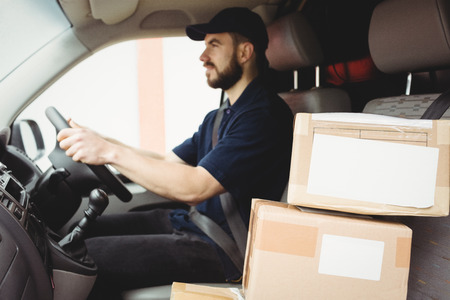 loading bay: Delivery man driving his van with packages on the front seat