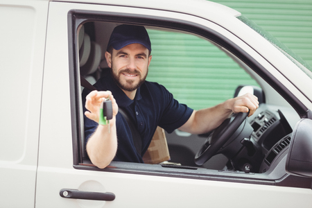 Delivery man sitting in his van while holding keys