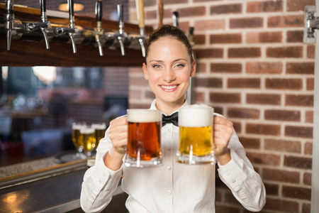 beers: Attractive female bartender holding two beers in a pub