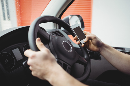 loading bay: Delivery man driving his van while using smartphone