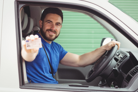 loading bay: Delivery man sitting in his van while showing his driving licence Stock Photo