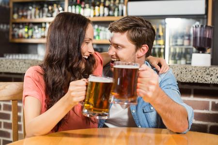 toasting: Couple toasting with beers at a bar