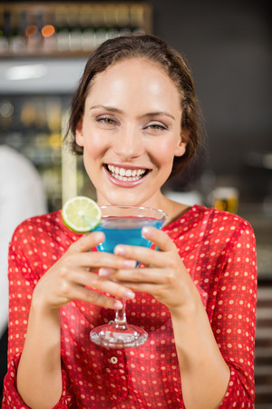 facing to camera: Smiling woman holding cocktail while facing camera in a bar
