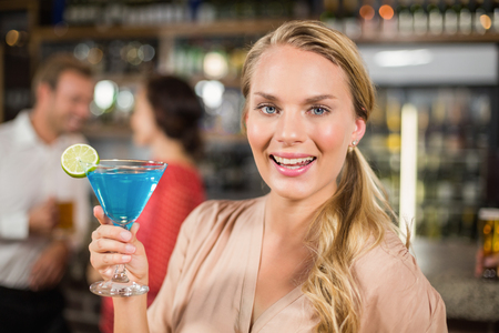 facing to camera: Attractive woman holding cocktail glass in a bar facing camera Stock Photo