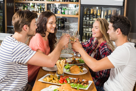 amused: Friends toasting with white wine at bar Stock Photo