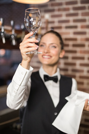 noting: Beautiful barmaid looking at a shiny wine glass