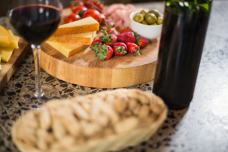 buch: Wine bottle with a glass and a buch of food in a bar