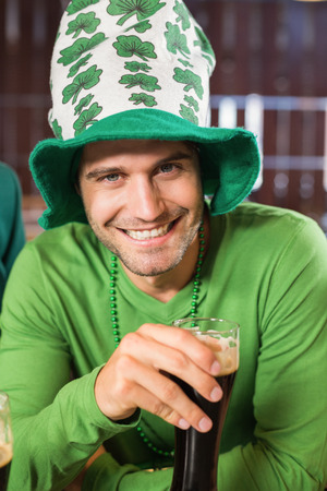 st  patty: Smiling man with a hat toasting a beer in a bar Stock Photo