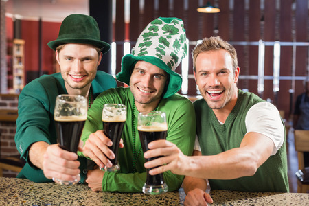 saint patty: Men toasting with beers in a bar