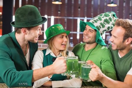 st  patty: Friends wearing St. Patricks day associated clothes toasting in a bar