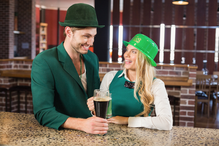 saint patty: Man and woman looking at each other while holding beers in a bar Stock Photo