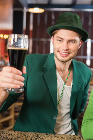 st  patty: Man with a hat toasting a beer in a bar