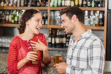 facing each other: Attractive couple facing each other with beers in hand