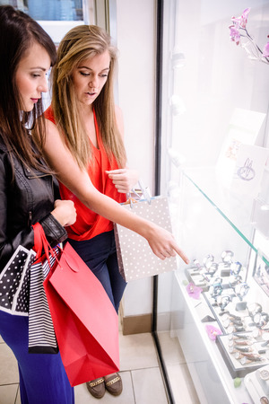 selecting: Two beautiful women selecting a wrist watch in a shop Stock Photo