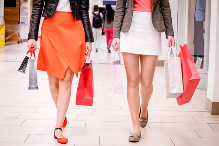 weekend activity: Women walking with bags while shopping in mall