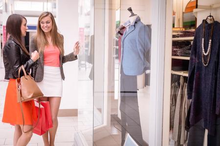 mujeres elegantes: Dos hermosas mujeres con bolsas de la compra ventana de compras en el centro comercial