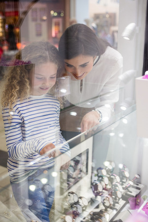 wrist watch: Mother and daughter selecting a wrist watch from a display of watches in shop