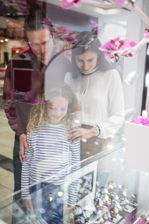 wrist watch: Happy family standing in front of shop window and looking at the wrist watch Stock Photo