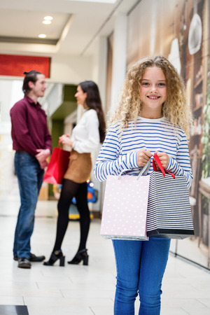 weekend activity: Happy girl holding shopping bag in mall and parents standing behind