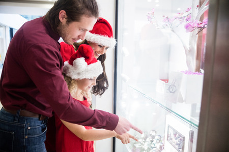 wrist watch: Family in Christmas attire looking at a display of wrist watch in shop Stock Photo