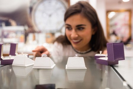 jewelry store: Happy woman selecting a finger ring in a jewelry shop Stock Photo