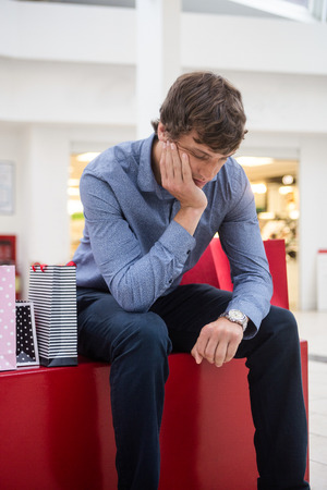 chin: Tired man sitting in shopping mall with hand on chin Stock Photo