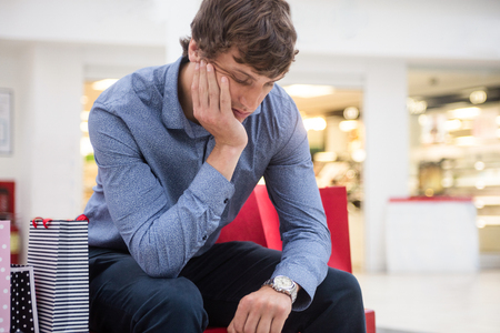 formals: Tired man sitting in shopping mall with hand on chin Stock Photo