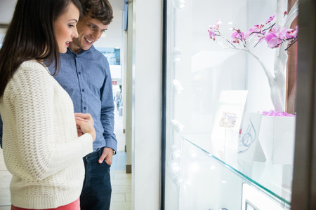 showpiece: Couple looking at window display in shopping mall