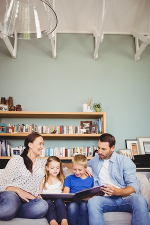 family sofa: Smiling family reading book while sitting on sofa at home Stock Photo