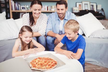 unwholesome: Smiling family with pizza on table at home