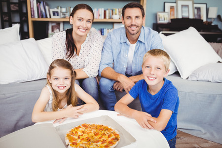 unwholesome: Portrait of smiling family with pizza on table at home