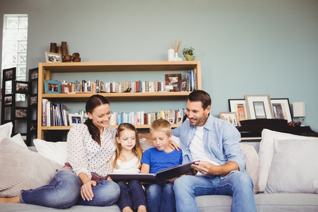 family sofa: Happy family reading book while sitting on sofa at home