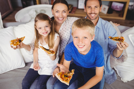 unwholesome: Portrait of smiling family holding pizza slices while sitting on sofa at home