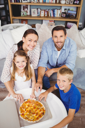 unwholesome: High angle portrait of family with pizza on table at home