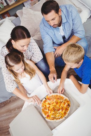 unwholesome: High angle view of family taking pizza slices on table at home Stock Photo