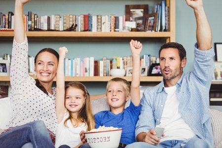 family sofa: Cheerful family with arms raised while sitting on sofa at house