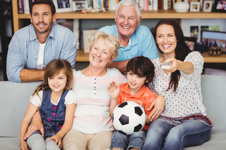 watching football: Smiling family watching football match at home