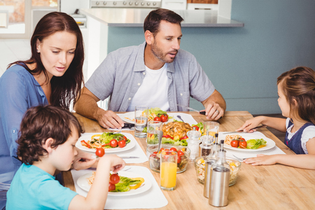 Family having lunch while sitting at dining table in home