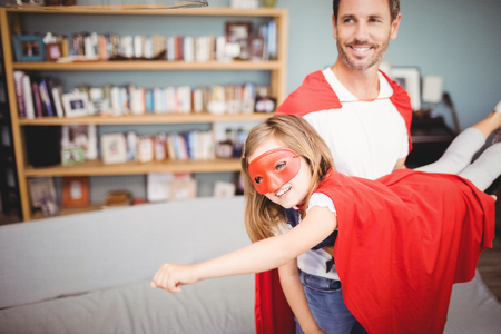 fun activity: Smiling father holding daughter wearing superhero costume at home