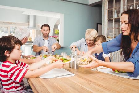 tomando refresco: Madre dar de comer al hijo mientras está sentado en la mesa de comedor con la familia Foto de archivo