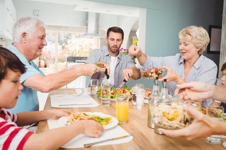tomando refresco: Granny dar de comer al abuelo mientras está sentado en la mesa de comedor con la familia