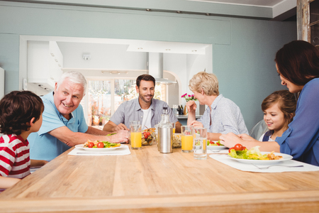 multi family house: Family with grandparents discussing at dining table in home