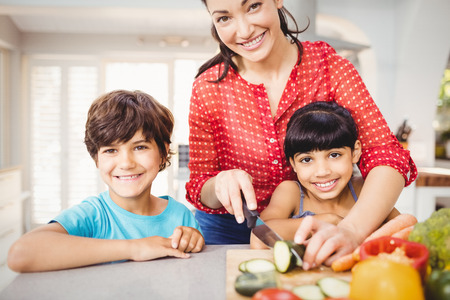 Portrait of happy woman with children chopping vegetables at home
