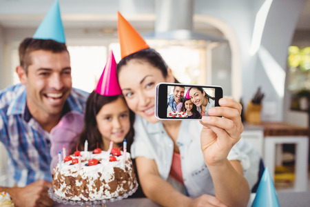 Close-up of cheerful family taking selfie during birthday celebration at home Stock Photo