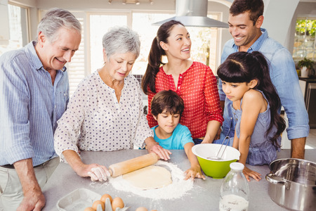 Senior woman preparing food with happy family at home