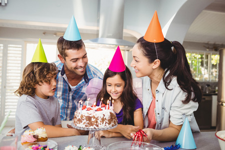 children celebration: Cheerful family with cake at table during birthday celebration