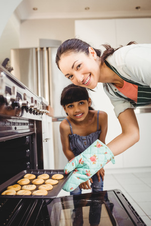 by placing: Portrait of happy woman with daughter placing cookies in oven at home