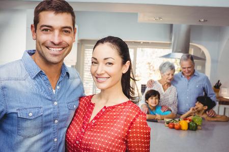 Retrato de primer plano de la feliz pareja con la familia preparando la comida en el fondo